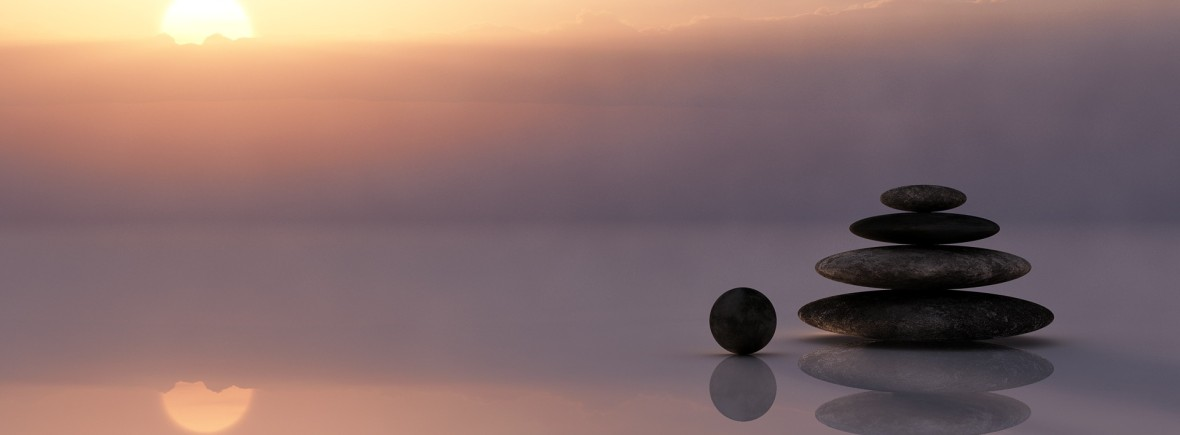 A sunset with a stack of rocks in a reflection