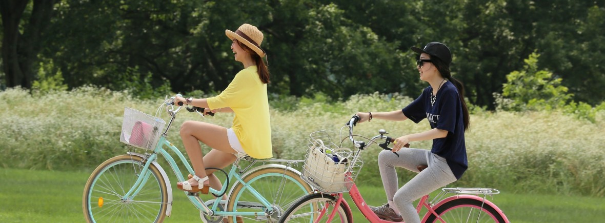 Two people leisurely riding bikes along a paved path