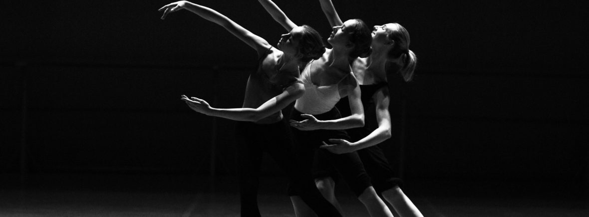 Three cordonated women doing ballet in black and white
