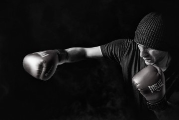 man with boxing gloves punching the air in grayscale