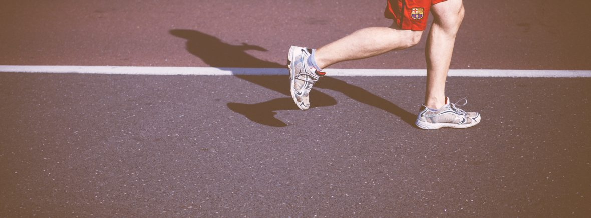 A man running with red pants on a track