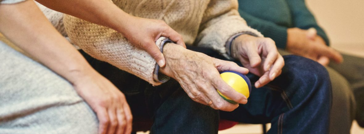 An older woman holds on to an older man's arm with a ball in it while they are sitting down