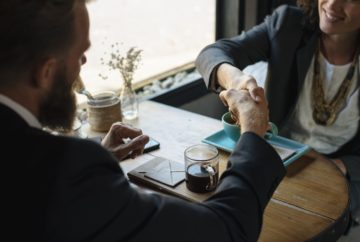 A businesswoman and businessman shake hands over coffee or tea