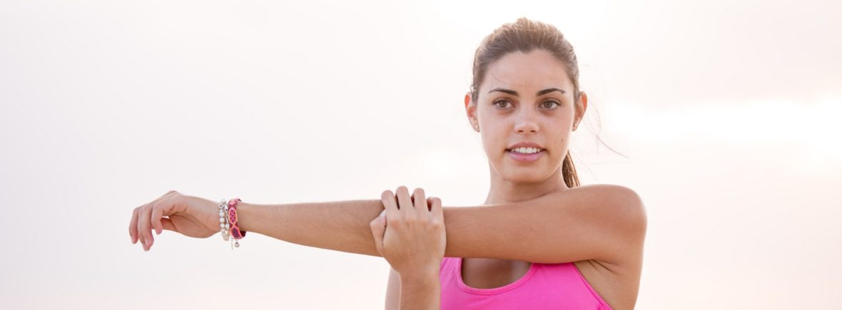 Woman in pink doing arm streaches