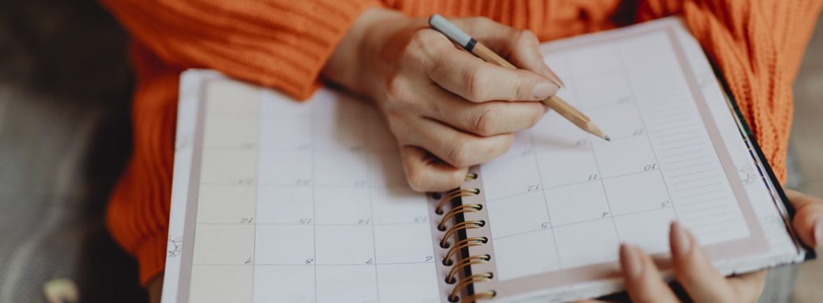 Woman with an orange shirt writing in an calendar planner