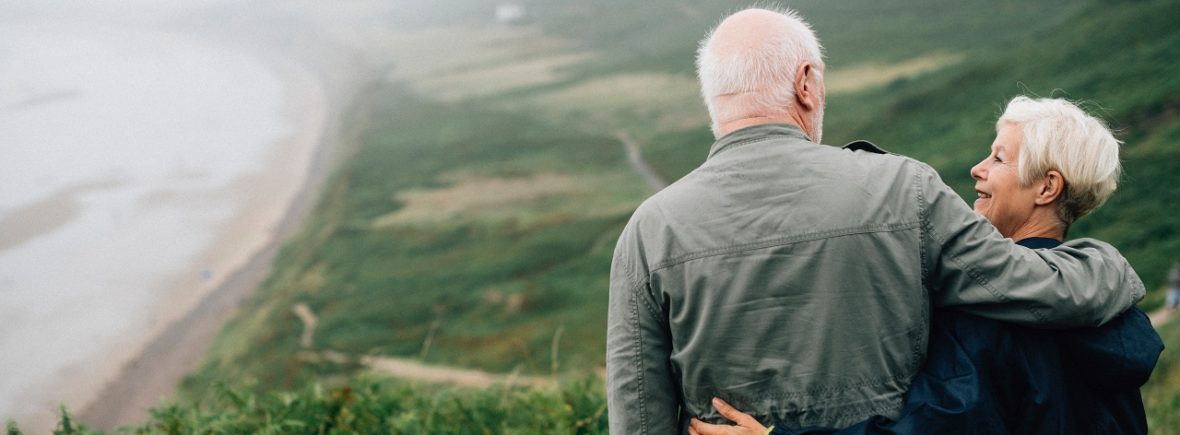 A sweet elderly couple on a green mountain with a view of a misty ocean